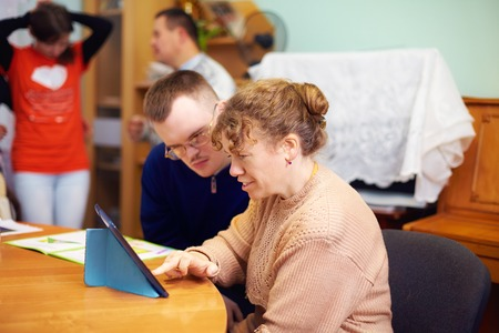 Foto de two friends with disability in rehabilitation center, watching digital tablet - Imagen libre de derechos