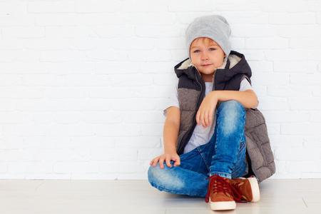 Photo pour portrait of fashionable kid near the wall - image libre de droit