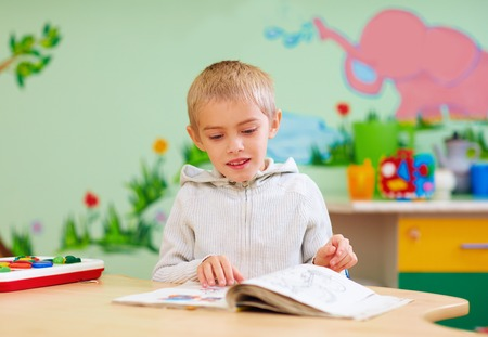 Photo pour cute boy, kid with special needs looking at a book, in rehabilitation center - image libre de droit