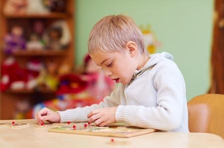 Foto de cute boy, kid with special needs solving a puzzle in rehabilitation center - Imagen libre de derechos