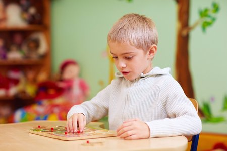 Photo pour cute boy, kid with special needs solving a puzzle in rehabilitation center - image libre de droit