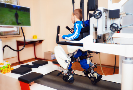 Photo pour young boy passes robotic gait therapy in rehabilitation center - image libre de droit