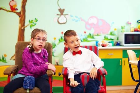 Foto de cute kids in wheelchairs at kindergarten for children with special needs - Imagen libre de derechos