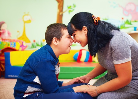 Foto de soulful moment. portrait of mother and her beloved son with disability in rehabilitation center - Imagen libre de derechos