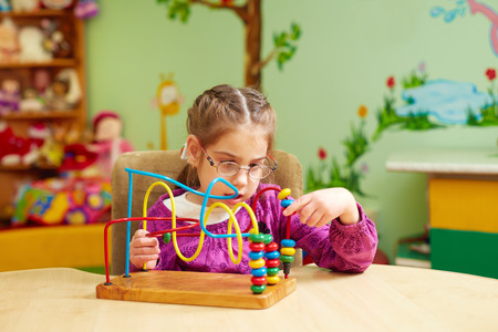 Photo pour cute little girl playing with developing toy in kindergarten for kids with special needs - image libre de droit