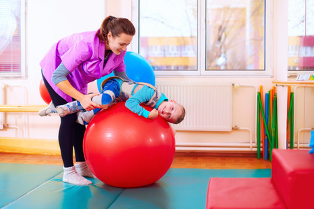 Foto de cute kid with disability has musculoskeletal therapy by doing exercises in body fixing belts on fit ball - Imagen libre de derechos
