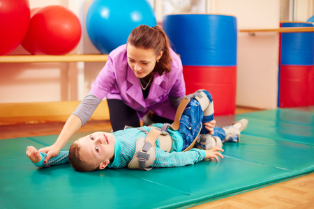 Foto de cute kid with disability has musculoskeletal therapy by doing exercises in body fixing belts - Imagen libre de derechos