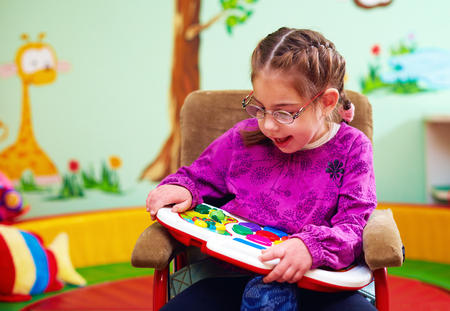 Photo pour cute girl in wheelchair playing with developing toy in kindergarten for children with special needs - image libre de droit