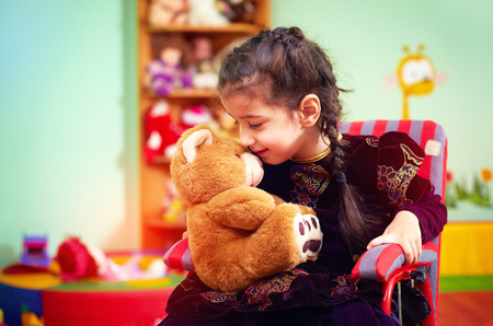 Photo for cute little girl in wheelchair telling her secret to plush bear in kindergarten for kids with special needs - Royalty Free Image