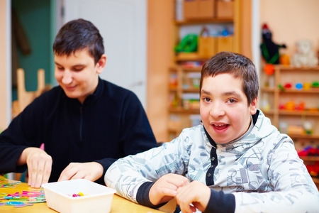 Foto de happy kids with disability develop their fine motor skills at rehabilitation center for kids with special needs - Imagen libre de derechos