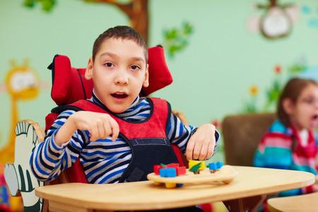 Foto de cheerful boy with disability at rehabilitation center for kids with special needs - Imagen libre de derechos