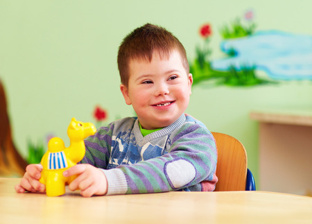 Foto de cute kid with down's syndrome playing in kindergarten - Imagen libre de derechos