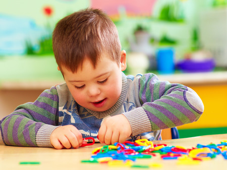 Photo for cute kid with down's syndrome playing in kindergarten - Royalty Free Image