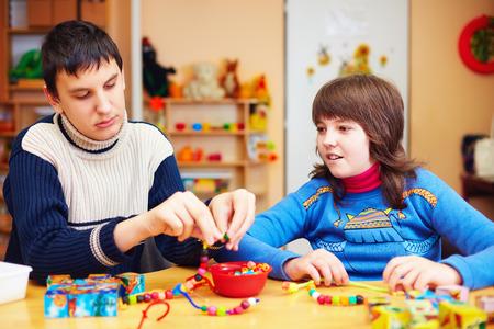 Foto de kids with special needs develop their fine motor skills in daycare rehabilitation center - Imagen libre de derechos