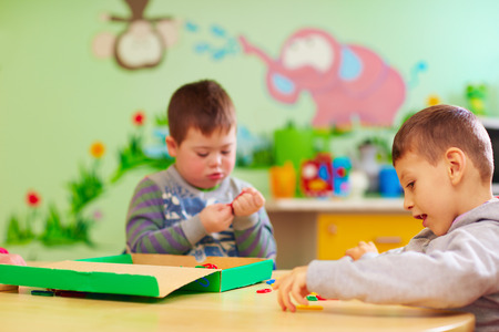 Foto de kids with special needs develop their fine motility skills in daycare rehabilitation center - Imagen libre de derechos