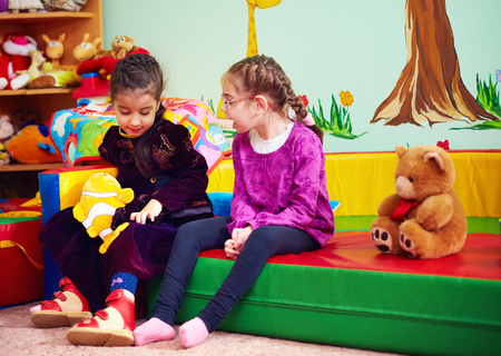 Foto de cute girls talking and playing in kindergarten for kids with special needs - Imagen libre de derechos