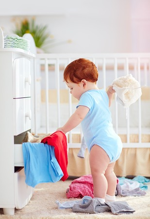 Photo for funny infant baby throwing out clothes from the dresser at home - Royalty Free Image