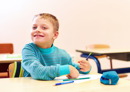 Foto de cute boy with special needs writing letters while sitting at the desk in class room - Imagen libre de derechos