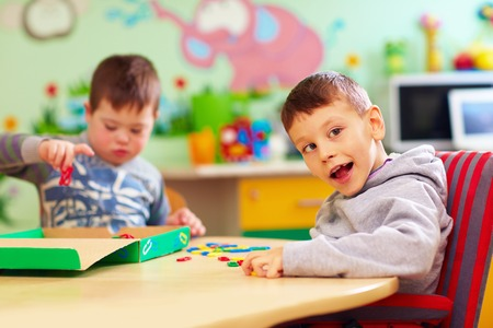 Foto de cute kids with special needs playing with developing toys while sitting at the desk in daycare center - Imagen libre de derechos