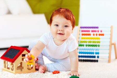 Photo pour cute redhead baby playing with wooden toys, numerals, learning to count - image libre de droit