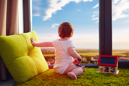 Photo pour infant baby sitting on carpet at home and watches the beautiful cityscape through the window - image libre de droit