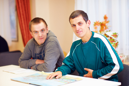 Foto de cheerful adult men with disability sitting at the desk in rehabilitation center - Imagen libre de derechos