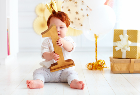 Photo for cute little baby boy holding number one, while sitting on party background - Royalty Free Image