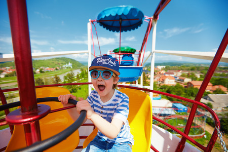 Photo for excited kid riding on ferris wheel in amusement park - Royalty Free Image