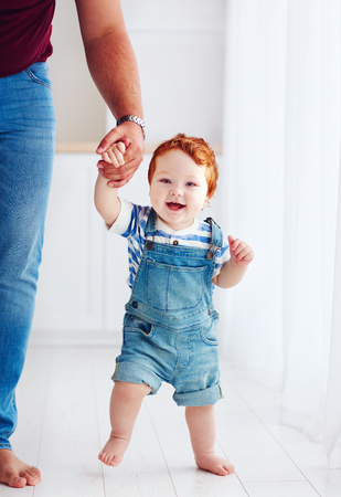 Photo for adorable happy toddler boy walking with the help of the father - Royalty Free Image