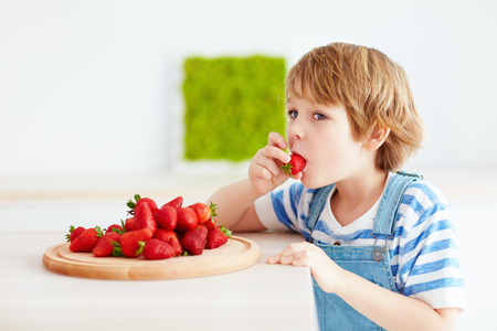 Photo for cute happy kid eating tasty ripe strawberries on the kitchen - Royalty Free Image