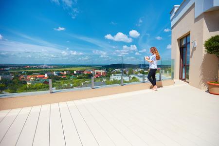 Foto de girl enjoying beautiful view on city in valley standing on modern rooftop terrace - Imagen libre de derechos