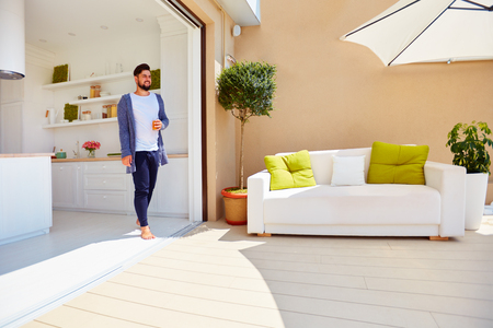 Photo for handsome man enjoys life on rooftop terrace, with open space kitchen and sliding doors - Royalty Free Image