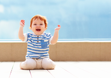 Photo pour cute excited toddler baby having fun on decking - image libre de droit