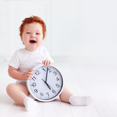 Foto de happy little toddler baby holding circle clock - Imagen libre de derechos