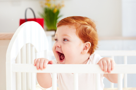 Photo for poprtait of cute happy infant baby standing in a cot at home - Royalty Free Image