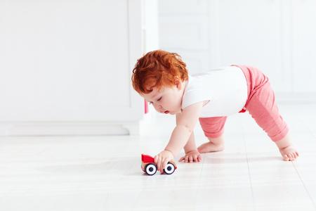 Foto de cute redhead baby boy rolling a toy car on the floor - Imagen libre de derechos