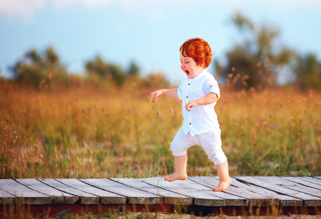 Photo for happy toddler baby running the path on summer field - Royalty Free Image