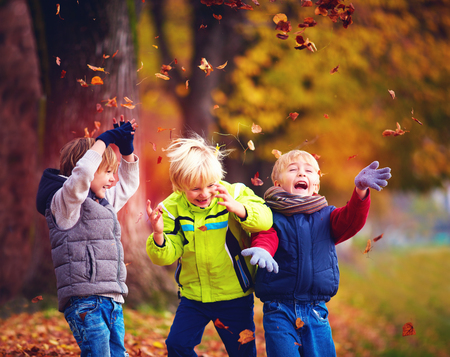 Photo for happy friends, school children having fun in autumn park among fallen leaves - Royalty Free Image