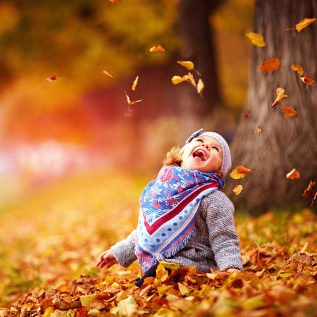 Photo pour adorable happy baby girl catching the fallen leaves, playing in the autumn park - image libre de droit