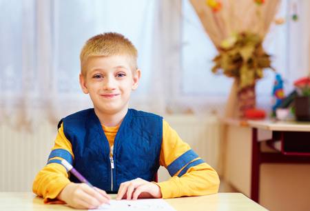 Foto de cute kid with special need sitting at the desk in classroom - Imagen libre de derechos