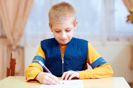Foto de cute kid with special need sitting at the desk , writing in notebook in classroom - Imagen libre de derechos