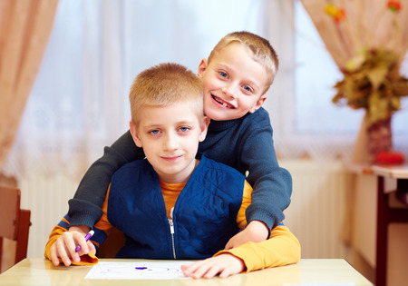 Foto de two cute kids, friends in rehabilitation school for kids with special needs - Imagen libre de derechos
