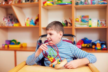 Foto de cheerful boy with disability at rehabilitation center for kids with special needs, solving logical puzzle - Imagen libre de derechos