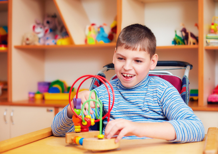 Foto de cheerful boy with disability at rehabilitation center for kids with special needs, solving logical puzzle - Imagen libre de derechos