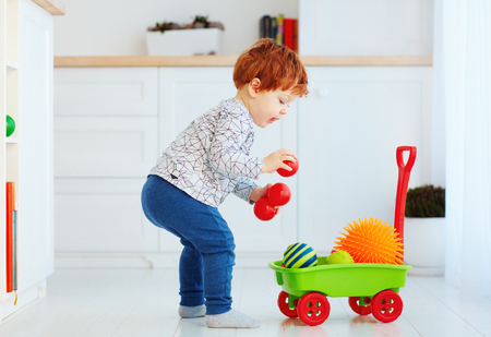 Photo pour cute redhead toddler baby collecting different balls into toy pushcart - image libre de droit