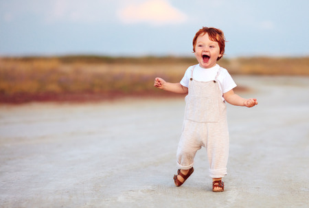 Foto de adorable redhead toddler baby boy in jumpsuit running through the summer road and field - Imagen libre de derechos