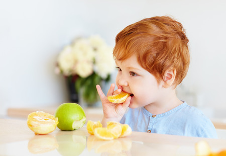 Photo for cute redhead toddler baby tasting orange slices and apples at the kitchen - Royalty Free Image