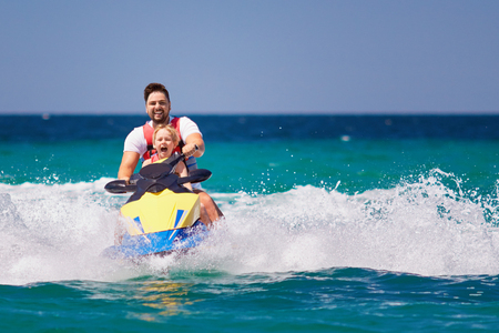 Photo pour happy, excited family, father and son having fun on jet ski at summer vacation - image libre de droit