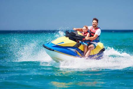 Foto per happy, excited family, father and son having fun on jet ski at summer vacation - Immagine Royalty Free
