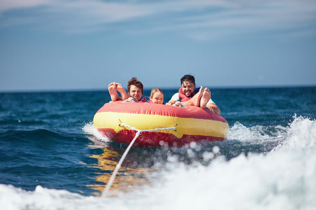 Photo for excited friends, family having fun, riding on water tube during summer vacation - Royalty Free Image